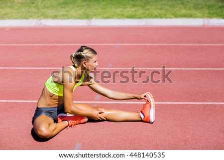 Female athlete warming up on the running track on a sunny day