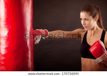 Female athlete with a punching bag - stock photo