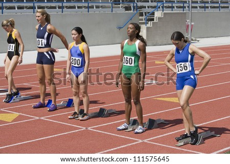 Female athletes at starting line ready to race - stock photo