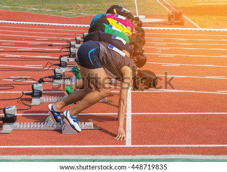 Female athletes preparing for race on starting blocks in stadium