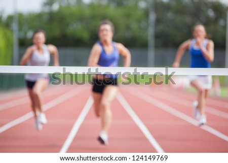 Female athletes racing towards finish line at track field - stock photo