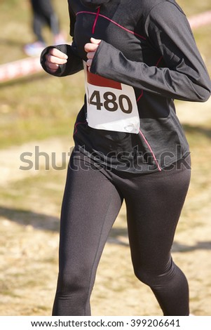Female athletic runner on a cross country race. Outdoor circuit. Vertical