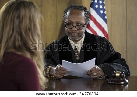 Female attorney addressing an African American judge in court - stock photo