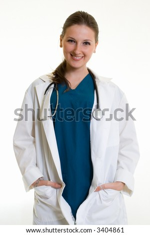 Female attractive doctor wearing white lab coat with hands in pockets wearing a stethoscope around shoulders smiling standing on white background