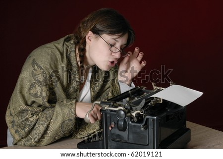 female author typing on an old typewriter,looking trough her glasses and making funny faces - stock photo