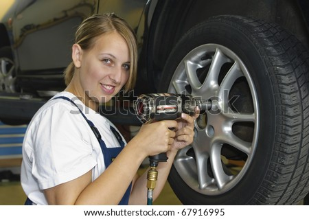 Female auto mechanic changing a wheel in a car in the garage with an impact wrench and smiling at the camera - stock photo