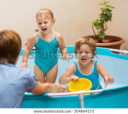 Female baby-sitter with little girls at inflatable pool - stock photo
