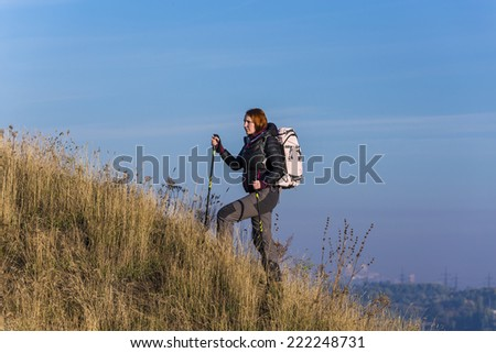 Female backpacker ascends steep hill. Grassy terrain, deep blue sky on the background - stock photo