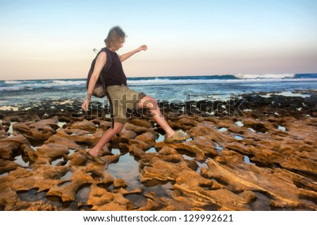 Female backpacker walks on sunset rocky beach. Shot in Sodwana Bay Nature Reserve, KwaZulu-Natal province, Southern Mozambique area, South Africa. - stock photo