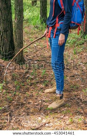 Female backpacker with branch in casual clothes in forest