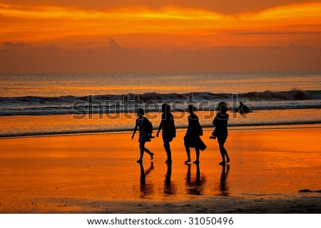 Female backpackers taking a stroll on Double Six beach, Seminyak, Bali, Indonesia. - stock photo