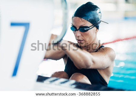 Female backstroke swimmer starting the race - stock photo