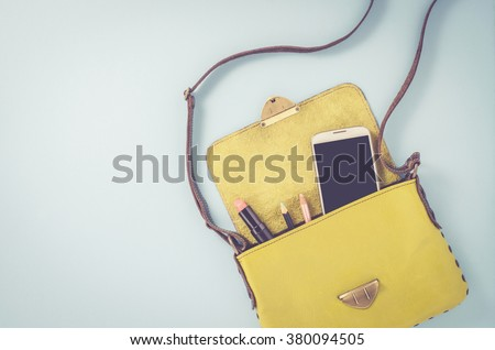 Female bag with smart phone and cosmetics - stock photo
