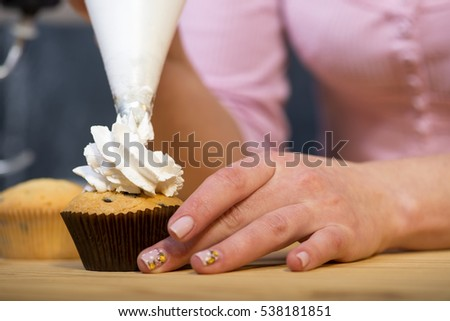 Female baker hands decorating cupcakes
