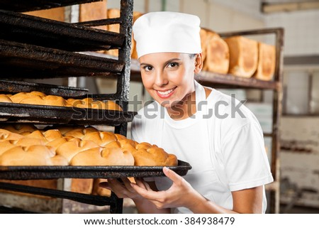 Female Baker Holding Baking Tray By Rack In Bakery - stock photo