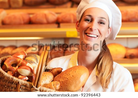 Female baker or saleswoman in her bakery selling fresh bread, pastries and bakery products in basket - stock photo