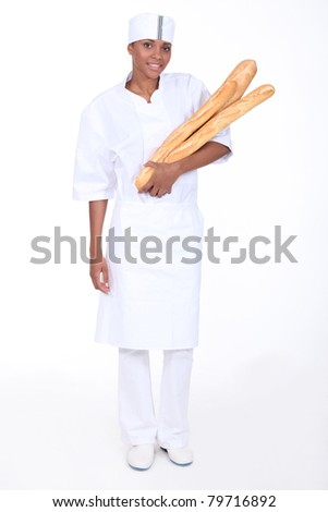 Female baker with loaves of bread - stock photo