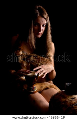 Female barbarian in foxcase with  tambourine at dark - stock photo