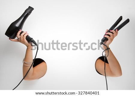 Female barber with hairdryer and curling iron in a hands through the holes on a white background - stock photo