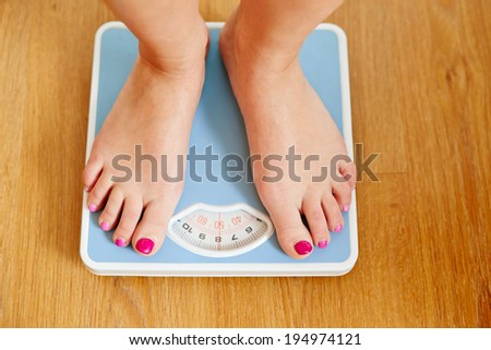 Female bare feet with weight scale on wooden floor - stock photo