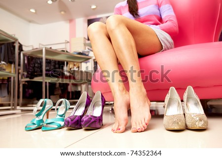 Female bare legs between pairs of shoes