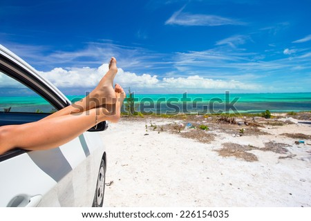 Female barefoot from the window of a car on background tropical beach - stock photo