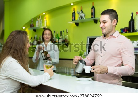 Female bartender and handsome male barista working at bar. Focus on man - stock photo