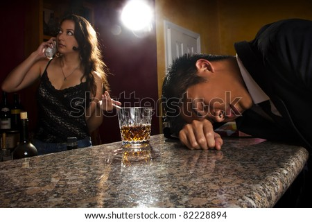 female bartender attending to drunk male customer - stock photo