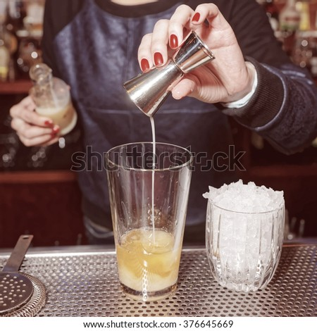 Female bartender is adding an ingredient to the glass, toned - stock photo