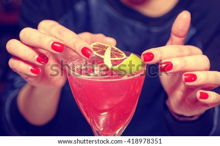 Female bartender is adding citrus zest to cocktail, toned image - stock photo