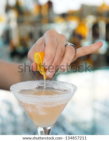 Female bartender is squeezing orange juice into a cocktail glass - stock photo