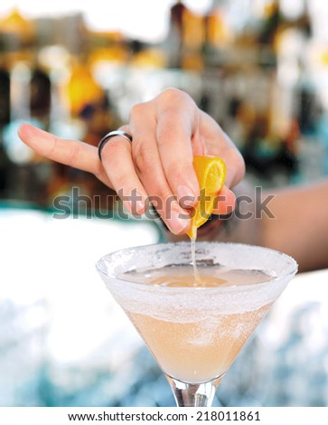 Female bartender is squeezing orange juice into a cocktail glass, toned image - stock photo