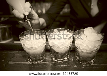 Female bartender pouring juice in glass, retro styled bar - stock photo