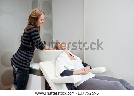 Female beautician washing hair of her customer before haircut at beauty salon - stock photo