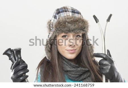 female beautiful skier wearing winter hat and black gloves. studio shot on gray background. skier holds ski sticks and ski. - stock photo