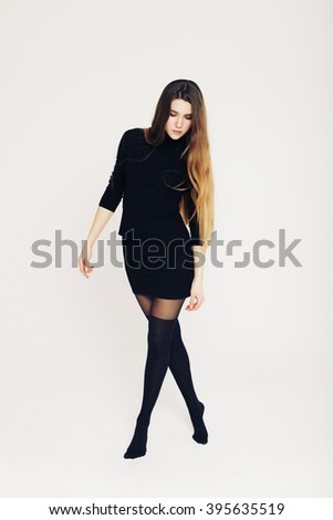 Female beauty concept. Portrait of fashionable young girl in black (socks) tights, a classic black turtleneck, tight black skirt over white background. Vogue style. Studio shot. - stock photo