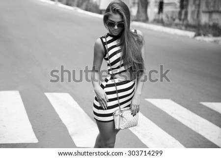 Female beauty concept. Portrait of fashionable young girl in casual (black and white) clothes, sunglasses and small bag posing on the street. Perfect hair & skin. Vogue style. outdoor shot - stock photo