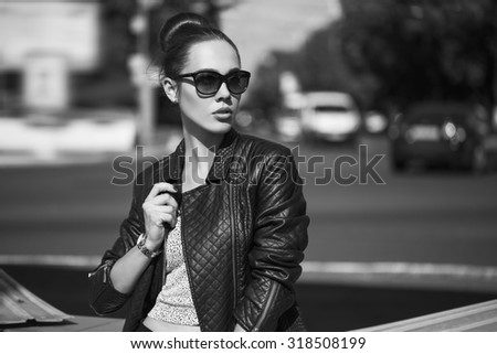 Female beauty concept. Portrait of fashionable young girl in casual black jeans, black jacket, white crop-top, sunglasses and small  bag posing on the street.  Vogue style. outdoor shot - stock photo