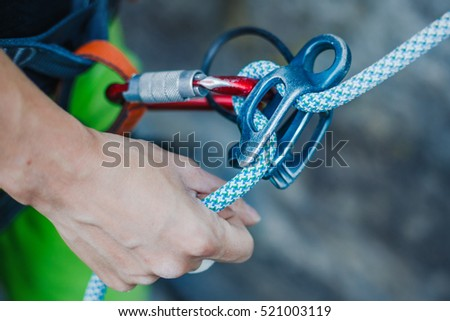 Female belayer with the rope and carabines