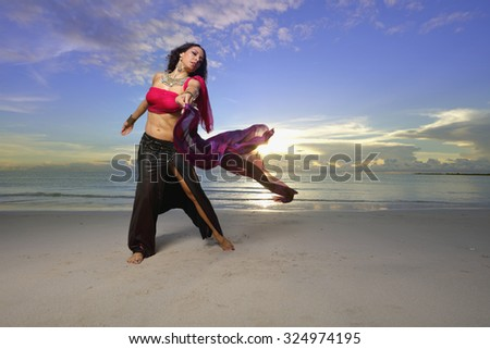 Female belly dancer on the beach stock image