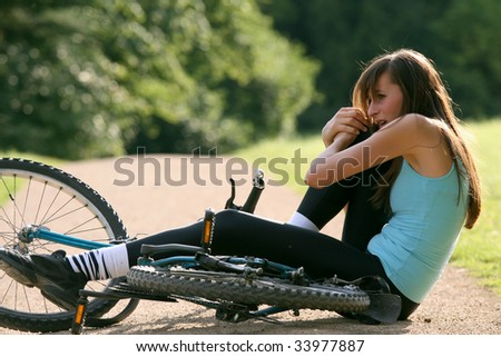 Female bike rider takes a tumble and crying from pain - stock photo