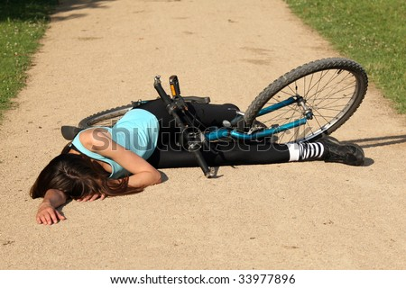 Female bike rider takes a tumble and lying unconscious on the road - stock photo