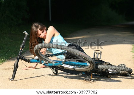 Female bike rider takes a tumble on the road - stock photo
