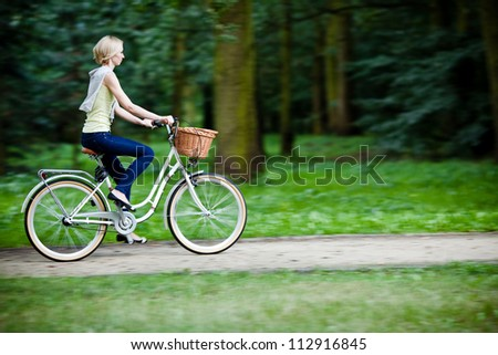 Female biker in a park, intentional motion blur (panning) - stock photo