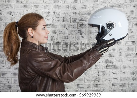 Female biker looking at white open helmet while holding in stretching arms, brick wall background