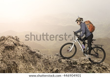 Female biker riding on bicycle in mountains on sunset - stock photo