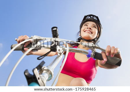 female biker starting to ride with blue sky background - stock photo