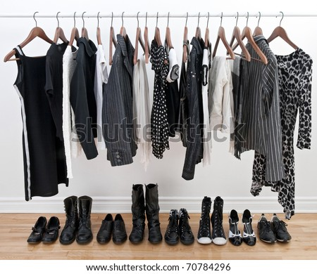 Female black and white clothes on a pole and shoes on a wooden floor. - stock photo