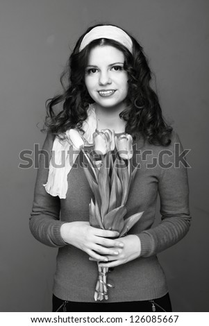 Female black and white portrait of young woman with tulips/Beautiful young girl with a bouquet of spring flowers