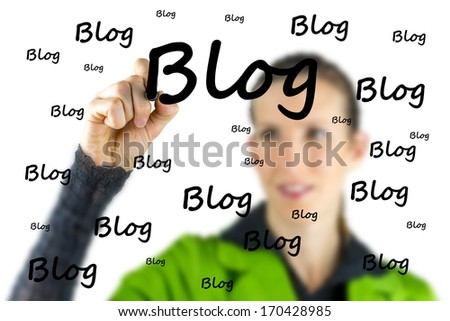 Female blogger writing the word Blog on a virtual interface with a marker pen as she extols the importance of communication and networking with the social community via a blog or diary - stock photo